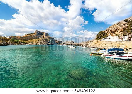 Lindos - View Of St. Paul Bay, Motor Boats Anchored Near Orthodox Church And Acropolis Of Lindos In