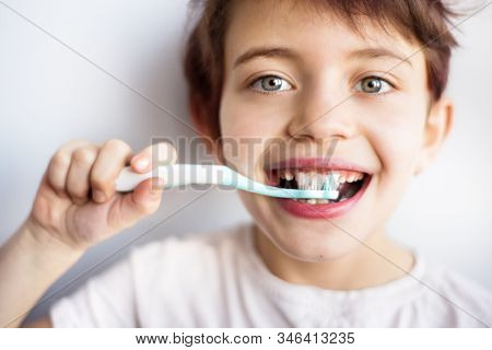 Closeup Horizontal Portrait Of Smiling Child Brushing Teeth With Blue And White Toothbrush. Dental A