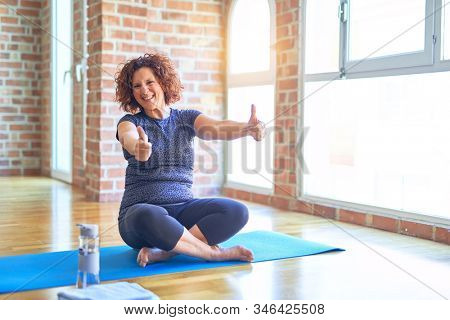 Middle age beautiful sportswoman wearing sportswear sitting on mat practicing yoga at home approving doing positive gesture with hand, thumbs up smiling and happy for success. Winner gesture.