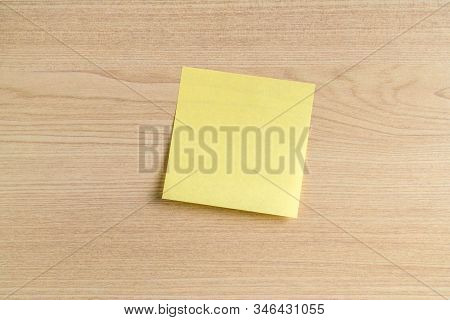 Blank Yellow Sticky Note, Post Note On Wooden Office Desk Background. Copy Space, Mockup