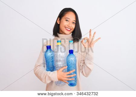 Young beautiful chinese woman recycling plastic bottles over isolated white background doing ok sign with fingers, excellent symbol