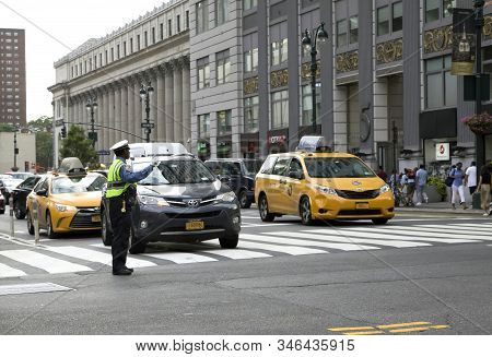 New York, New York/usa - July 2, 2019: Nypd Agent Directs Traffic Along Busy Manhattan Street.