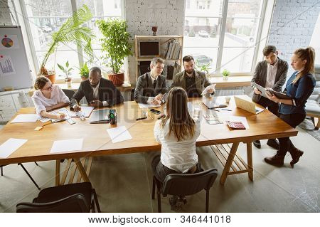 Top View. Group Of Young Business Professionals Having A Meeting. Diverse Group Of Coworkers Discuss