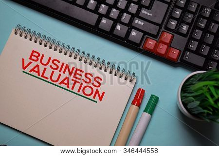 Business Valuation Write On A Book Isolated On Office Desk.