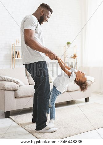 Black Dad Teaching Little Naughty Daughter Dancing At Home, Girl Staying On Father Feet And Having F