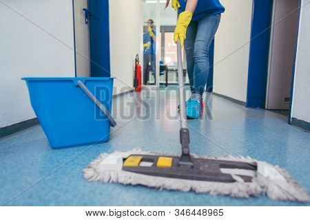 Close-up of cleaners moping the floor of a hall