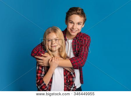 Siblings Love. Portrait Of Happy Kids Brother And Sister Hugging And Posing Together Over Blue Backg