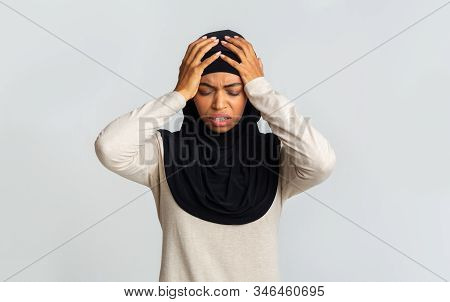 Acute Headache. Sick Black Muslim Lady In Headscarf Touching Her Head With Two Hands, Suffering From