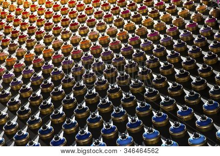 Rows Of Color Paint Spray Cans Placed On A Black Wall