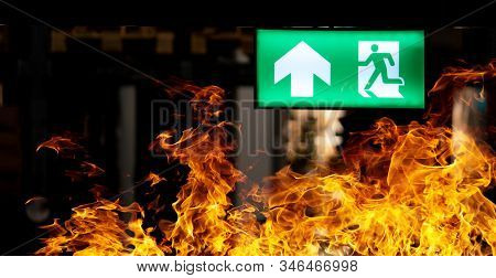 Hot Flame Fire And Green Fire Escape Sign Hang On The Ceiling In The Warehouse At Night. The Concept