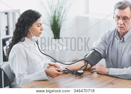 Hypertensive Crisis. Young Latina Nurse Measuring Blood Pressure Of Elderly Man At Clinic Office, Co