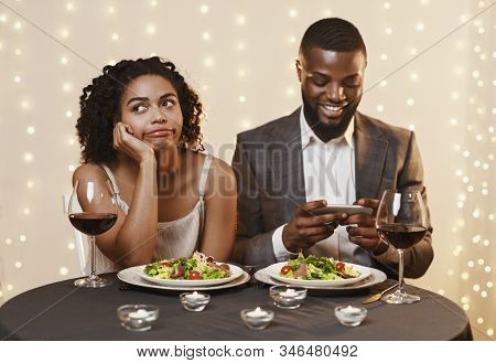 Bored Young Black Woman At Date In Restaurant, Afro Man Chatting On Mobile Phone