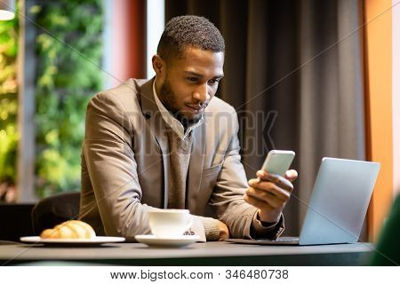Multitasking. Confident Black Businessman Using His Mobile Phone And Laptop For Work At Coffee Shop,