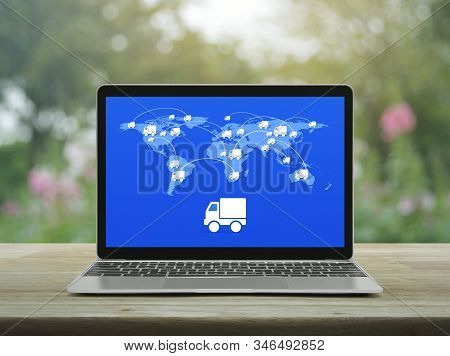 Delivery Truck Icon With Connection Line And World Map On Modern Laptop Computer Screen On Wooden Ta