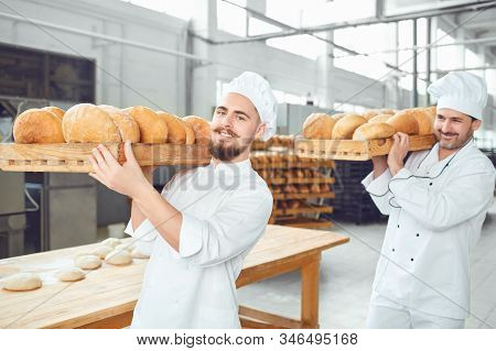 Two Bakers Men Carry Trays With Bread At The Bakery.