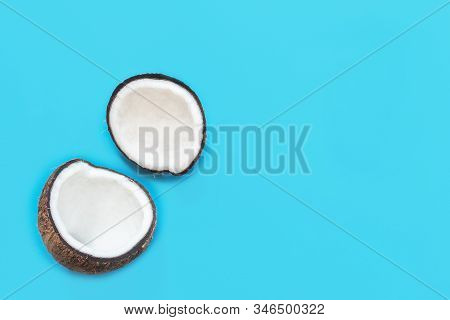 Two Halves Of Coconut, Open Coconut Cut In Half Isolated On Blue Background. Coconut Pulp Is Very He