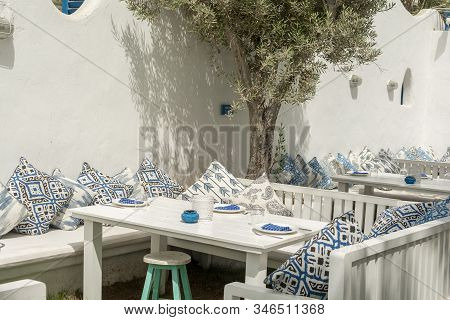 White Interior Of The Garden In Greek Mediterranean Style With White And Blue Main Color. Tables And