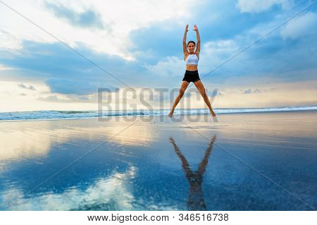 Young Woman Doing Jumping Jack Or Star Jumps Exercise To Burn Fat, Keep Fit. Sunset Beach, Blue Sky