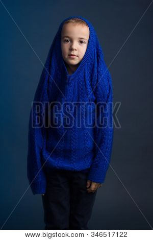 Studio Portrait Of Dark-haired Boy With Short Haircut In A Blue Classic Knitted Sweater Pulled Playf