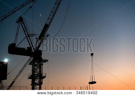 Silhouette Of Construction Tower Cranes Lifting Building Materials During Sunset - Industrial Crane
