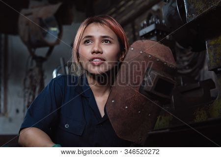 Diverse Female Industrial Engineer Holding Welding Helmet After Work Shift - Young Asian Factory Met