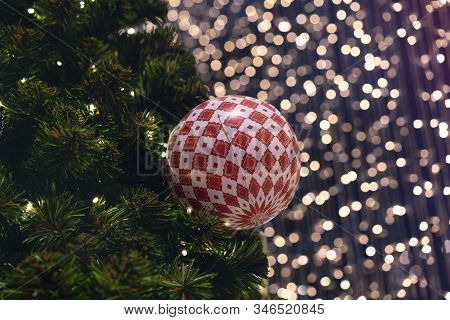 Christmas Ball Decoration Hanging On Festive Xmas Tree With Bokeh Out Of Focus Background Lights - C