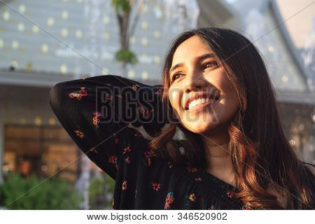 Asian Ethnicity Diverse Woman Smiling And Enjoying Afternoon Sunshine Outdoors - Headshot Of Carefre