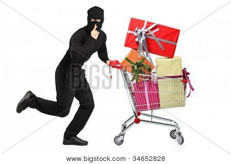 Full length portrait of a robber pushing a cart with finger on his lips gesturing silence isolated on white background