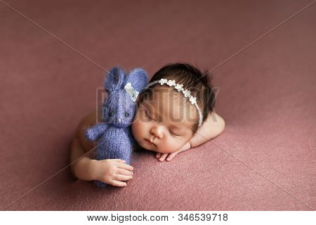 Adorable Cute Newborn Baby Girl With Knitted Toy Easter Bunny In Hands.  Lovely Child Playing With P