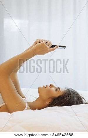 Beautiful Young Woman In Her Underwear Lying On Her Bed Using Her Smart Phone.