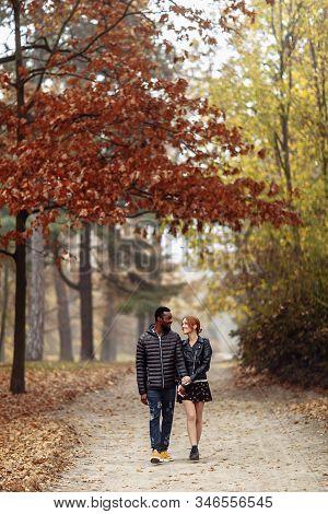 Happy Interracial Couple Walking In Autumn Park