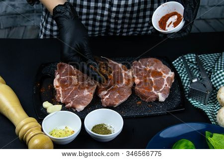 A Chef In Black Gloves Sprinkled With Red Pepper A Raw Tenderloin. Fresh Raw Pork Tenderloin On A Wo