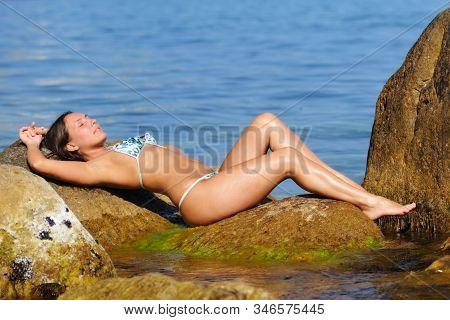 Girl In Swimsuit Posing On Big Boulder
