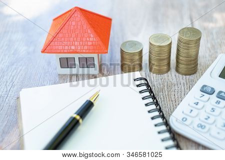 A Coin In A Hemp Bag Placed Near Orange Roof House Money Saving Ideas For Buying A Home Or Loan For