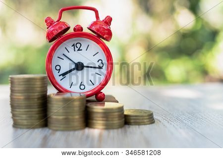 A Red Alarm Clock And A Pile Of Coins Resting On The Table. Ideas To Save Money, Ideas For Business