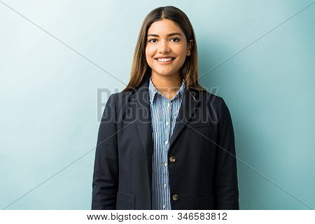 Smiling Young Female Professional Standing While Making Eye Contact Against Colored Background