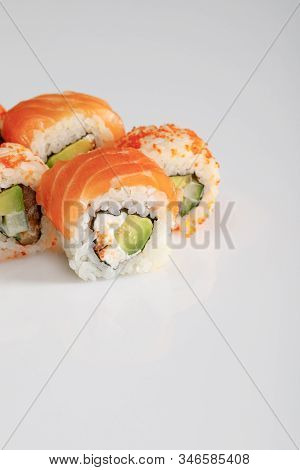 Close Up View Of Delicious Philadelphia And California Sushi With Salmon And Masago Caviar On White