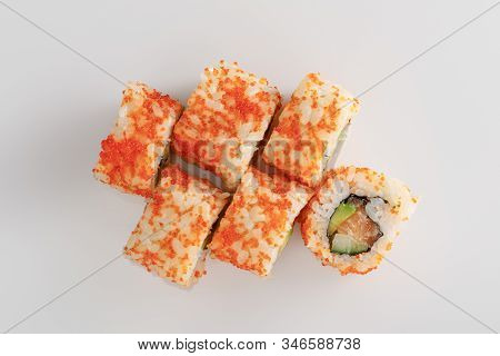 Top View Of Delicious California Roll With Avocado, Salmon And Masago Caviar On White Surface