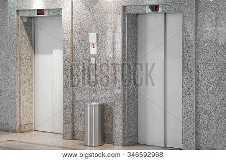 View Of Two Elevator Doors In Office Building. Wide Angle View Of Several Modern Elevators With Clos