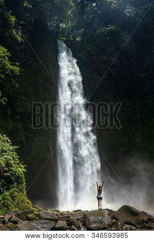 Adventure Seeker Standing Near The Beautiful Jungle Waterfall And Enjoying Nature.