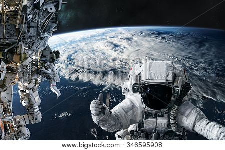 Astronauts And The Iss In Orbit Of The Planet Earth. Solar System. Science Fiction. Elements Of This