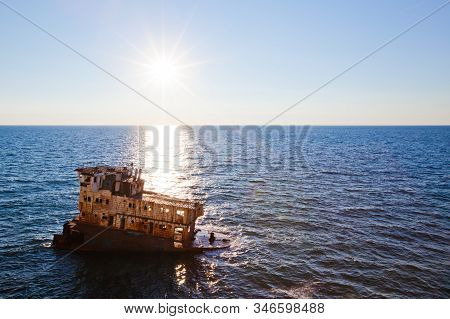 Sunken Rusty Cargo Ship In Still Blue Sea Waters With Bright Sun Over Water Horizon On Summer Clear