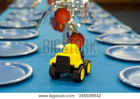 Boy Party Table Set Truck And Basketball Theme.  Empty Plates Line A Long Table Waiting For Children