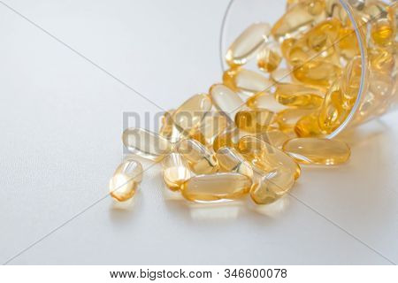 Supplements. Transparent Yellow Capsules On A White Background And Place For Text. Free Space. Amega