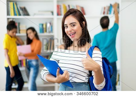 Happy Caucasian Female Student With Group Of Students At Classroom Of University