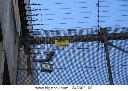 A Surveillance Camera And Spotlight Behind The Fences Of A Prison.