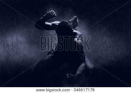 Thai Boxer In The Rain And Under A Blue Spotlight. Mongkhon. The Concept Of Victory In Competitions,