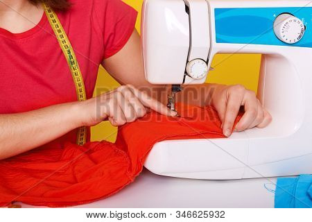 Image Of Seamstress Being At Her Workplace, Working Hard, Making Little Stitches Along Bright Red Fa