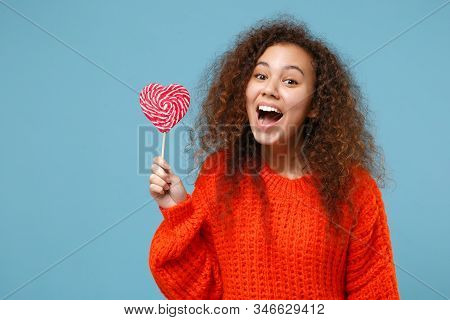 Cheerful Young African American Girl In Casual Orange Knitted Clothes Isolated On Pastel Blue Wall B