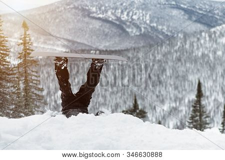 Snowboarder Feet Sticking Out Of The Snow On A Snowy Mountains Background.